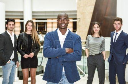 Photo pour Homme d'affaires confiant. Joyeux jeune homme africain en tenue de cérémonie gardant les bras croisés et souriants tandis que son collègue caucasien debout sur le fond - image libre de droit