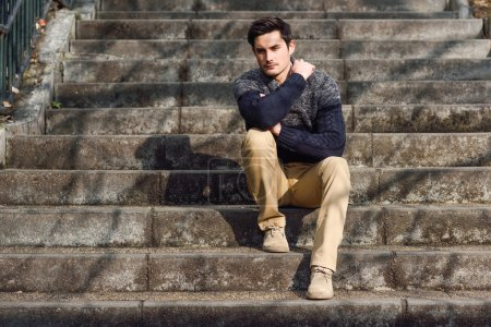 Photo for Portrait of a young handsome man, model of fashion, with modern hairstyle sitting on stairs, wearing casual clothes. - Royalty Free Image