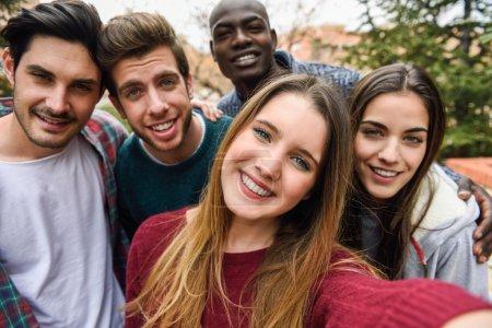 Photo pour Groupe multiracial d'amis prenant le selfie dans un stationnement urbain avec une jeune fille blonde au premier plan - image libre de droit