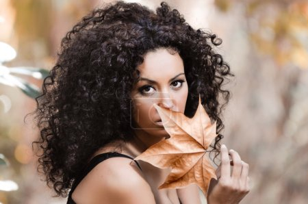 Photo for Young beautiful woman with a dry leaf in an urban park - Royalty Free Image