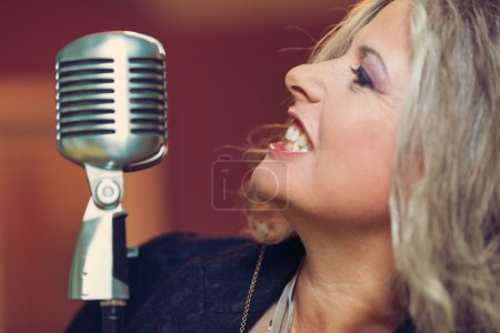 Woman with microphone sing in interior