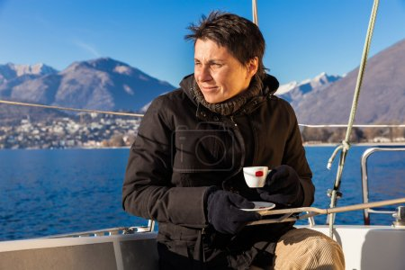 woman makes a coffee break on the sail boat