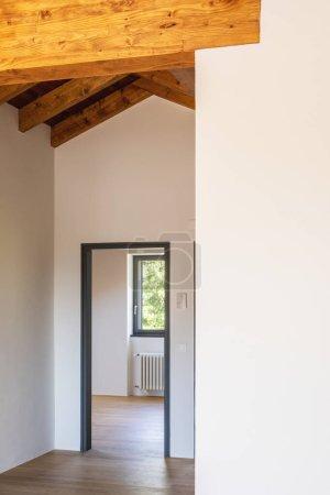 Photo pour Détail d'une porte ouverte, chambre blanche vide avec poutres apparentes et planchers de bois franc. Personne à l'intérieur. - image libre de droit