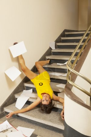Photo for Woman portrait at  staircase accident, dropped all papers - Royalty Free Image