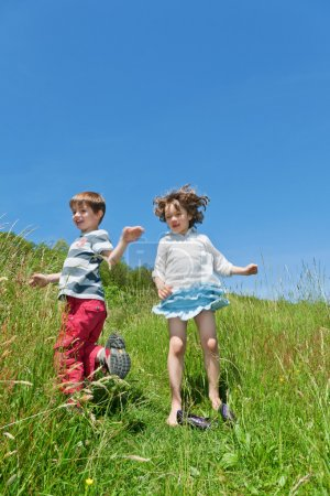 two children jumping in a meadow