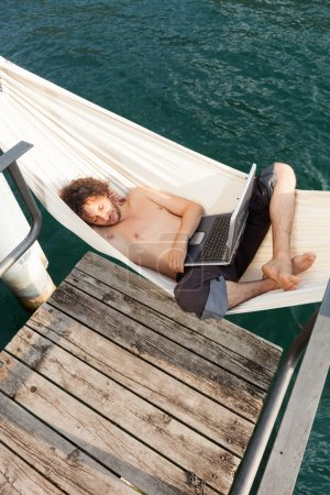 young man with laptop at lake