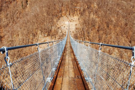 Photo for Mountain landscape with suspension bridge over the valley - Royalty Free Image