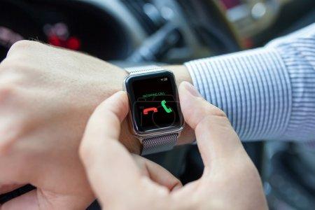 Photo pour Homme avec montre intelligente sur la main et appel entrant dans l'écran de conduite d'une voiture - image libre de droit
