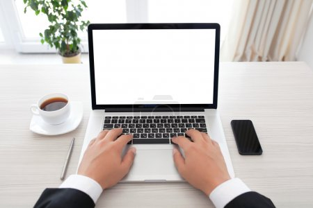 businessman sitting behind a laptop with isolated screen