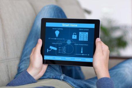 Photo pour Homme se trouvant sur un sofa et retenant une tablette avec la maison intelligente de programme sur l'écran - image libre de droit