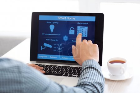 Photo for Man sitting at a laptop with the program smart home on the screen - Royalty Free Image