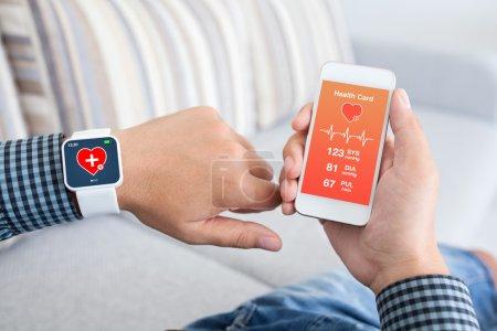 Photo pour Mains masculines retenant le téléphone tactile et la montre intelligente avec le capteur de santé d'application mobile - image libre de droit
