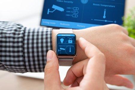 Photo pour Main de l'homme dans la montre avec maison futée de programme sur l'écran sur le fond de l'ordinateur - image libre de droit