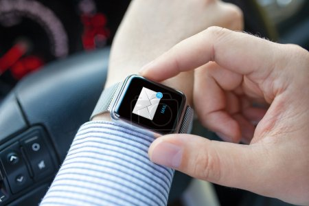 Man hand in car with watch and e-mail on screen