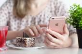 Žena držící v ruce iphone 6s Rose Gold v kavárně