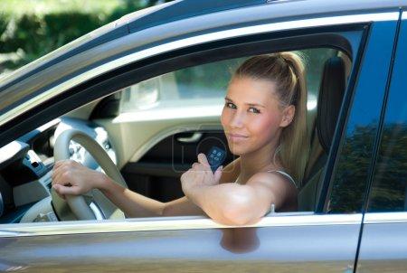 Photo pour Attrayant jeune fille en voiture avec sa nouvelle clé de voiture - image libre de droit