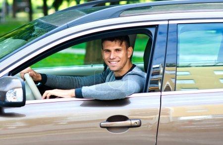 Photo pour Jeune homme au siège du conducteur de sa voiture regardant par la fenêtre - image libre de droit