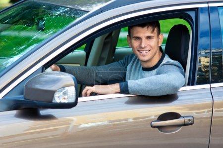 Photo pour Jeune homme au volant de sa voiture en regardant par la fenêtre - image libre de droit