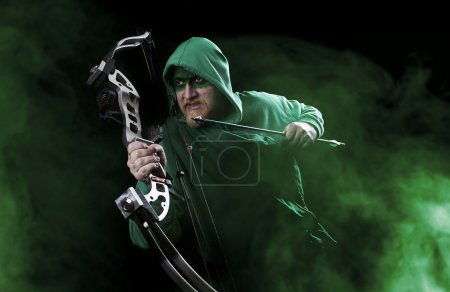 Man in green suit and mask holding bow and arrow...