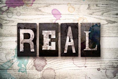 """Photo pour Le mot """"REAL"""" écrit en métal sale type typographie vintage sur un fond de bois blanchi à la chaux avec des taches d'encre et de peinture . - image libre de droit"""
