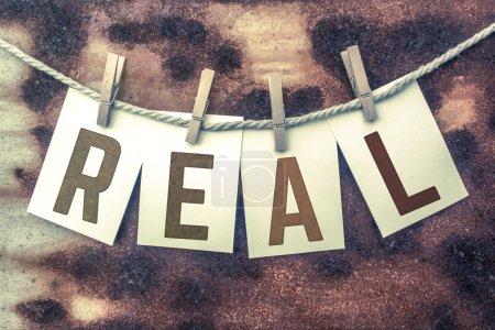 """Photo pour Le mot """"REAL"""" estampillé sur les cartes et épinglé sur un vieux morceau de ficelle sur un fond en métal rouillé . - image libre de droit"""