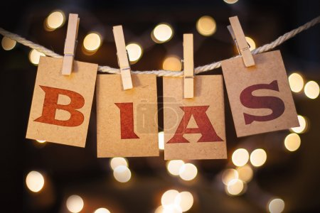 Photo for The word BIAS printed on clothespin clipped cards in front of defocused glowing lights. - Royalty Free Image
