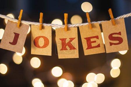 Photo pour Le mot Blagues imprimées sur des cartes découpées en épingle à linge devant des lumières lumineuses défocalisées. - image libre de droit