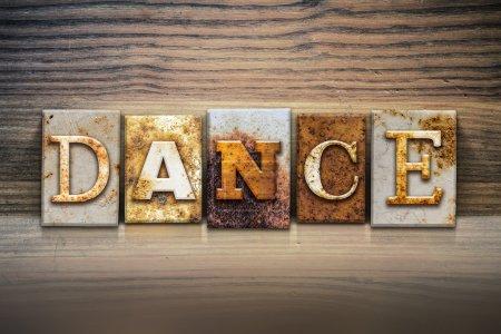 Photo pour Le mot « Dance », écrit en type de typographie métal rouillé, assis sur un fond de corniche en bois. - image libre de droit