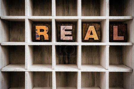 """Photo pour Le mot """"REAL"""" écrit à l'encre vintage type typographie en bois teinté dans le tiroir d'une imprimante cloisonnée . - image libre de droit"""