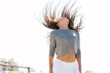 Photo for Attractive young woman flicking her hair up the the air against a sunny blue sky in celebration and joy, being spontaneous and expressive during a joyful happy summer day on holiday. Fun young lifestyle. - Royalty Free Image