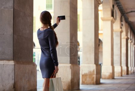 Photo for Rear view of a young elegant woman using her smartphone up and pointing it to take pictures while visiting a destination city on vacation. Technology and holiday travel lifestyle outdoors. - Royalty Free Image