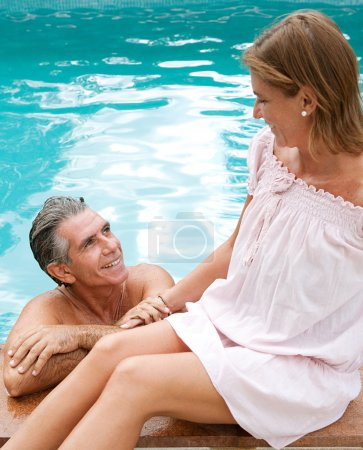 couple relaxing together on the egde of a swimming pool