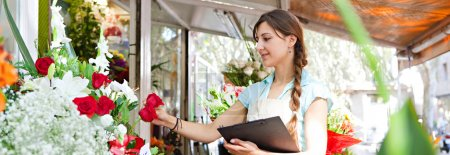 florist woman works in her store with a a clipboard