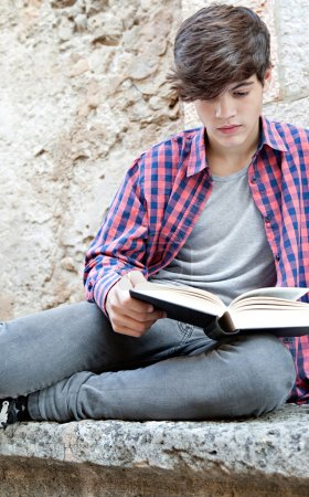student boy on a college campus reading a book