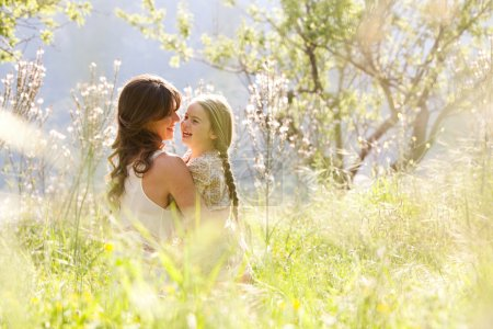 Photo for Young mother and child daughter together, hugging and joyfully laughing while relaxing in a golden field of sunshine and spring flowers while on a summer holiday. Family activities and outdoors lifestyle. - Royalty Free Image