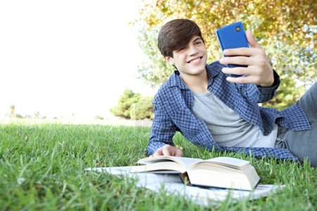 boy with his college books using a smartphone