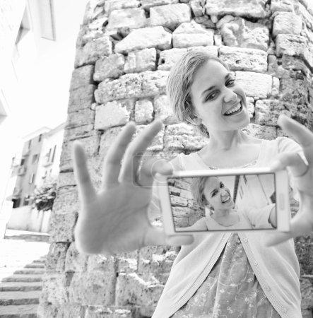 Photo pour Portrait noir et blanc de jeune touriste debout dans une rue pittoresque en pierre dans une ville de destination en vacances, tenant et utilisant un appareil smartphone pour prendre des photos selfies et réseau en ligne. Voyages et technologie . - image libre de droit