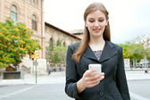 Businesswoman using smartphone in a classic city