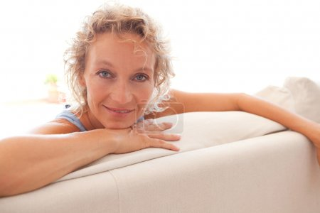 woman relaxing on a white sofa at home