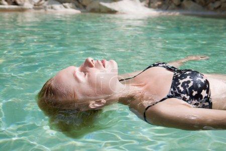 Photo pour Portrait de profil beauté d'une jolie femme blonde scandinave flottant dans une piscine d'eau transparent bleu en vacances pendant une journée d'été ensoleillée. Voyage et vacances en plein air de style de vie. - image libre de droit