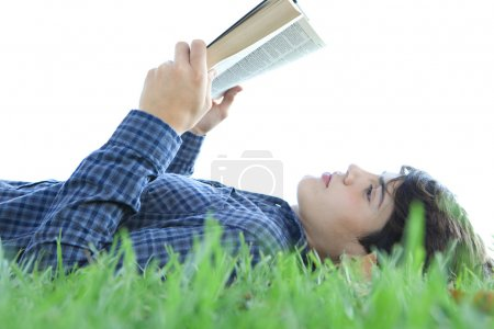 boy reading a book on the grass
