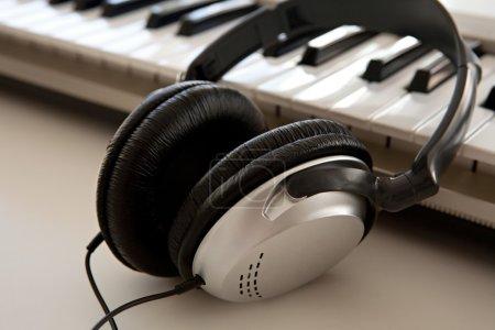 Photo pour Fermez-vous de nature morte vers le haut de deux dispositifs électroniques de musique et de bruit s'étendant ensemble sur un bureau blanc dans un studio d'enregistrement, intérieur. Vue détaillée d'une paire d'écouteurs et d'un clavier, technologie. - image libre de droit