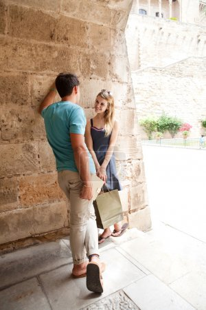 couple smiling against an wall and carrying shopping bags