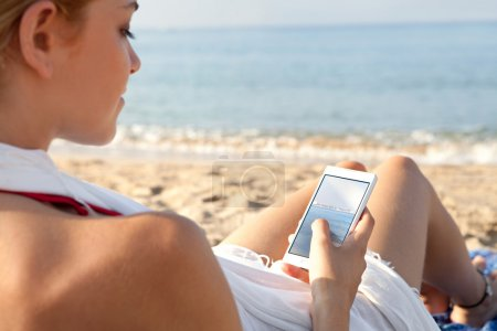 woman on a beach by the sea using a smartphone