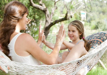 daughter and her mother clapping their hands on a hammock