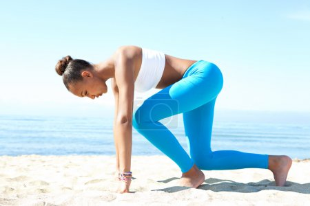 Photo for Side view of an attractive healthy young african american woman crouching in the ready position to start running exercise training against a blue sea and sky during a sunny day. Sport lifestyle outdoors. - Royalty Free Image
