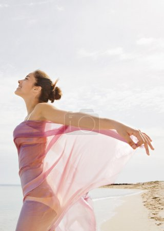 young woman with a pink fabric sarong on the beach