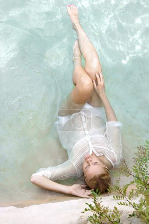 woman lying and relaxing in a swimming pool