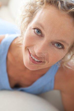 Photo pour Gros plan portrait de beauté d'une jolie femme en bonne santé d'âge moyen se détendre sur un canapé blanc à la maison, en regardant la caméra souriant. Intérieur maison vie et bien-être style de vie . - image libre de droit