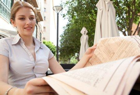 Photo pour Portrait d'une femme d'affaires séduisante assise dans un café terrasse buvant une boisson chaude, tenant et lisant un journal financier pendant une journée ensoleillée en ville, en plein air . - image libre de droit